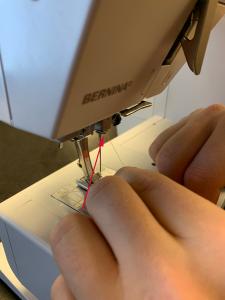Tråd går ned til trådholder i symaskinen.