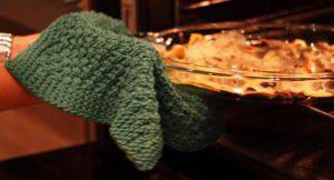Strikket gryteklut brukes til å ta ut lasagne fra ovnen.