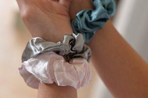 Rosa, grå og blå scrunchies på håndledd.